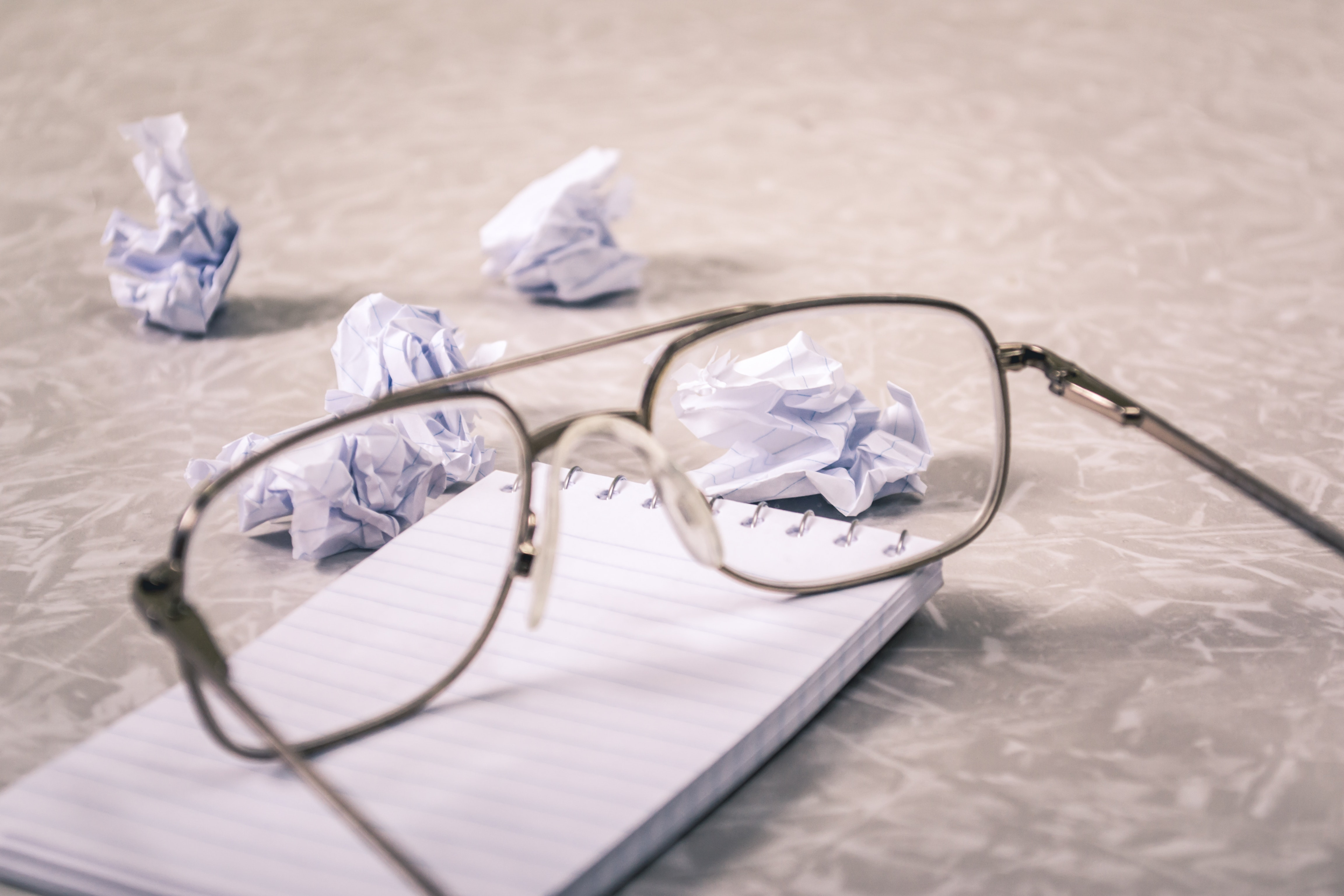 close up photography of eyeglasses near crumpled papers 963056